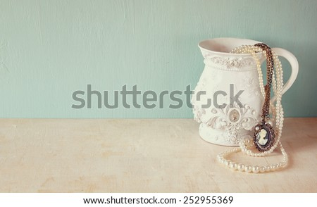 white classic victorian vase on wooden table with a collection of romantic vintage jewelry and pearls. retro filtered image. room for text  - stock photo
