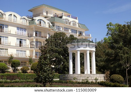 White classical gazebo and summer hotel resort in a formal garden - stock photo
