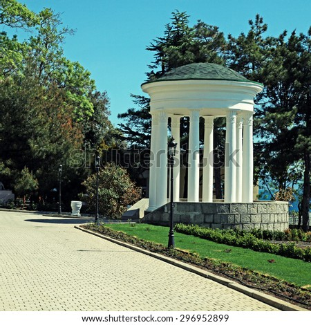 White classical rotunda and footpath in summer ornamental garden. Square toned image, instagram effect - stock photo