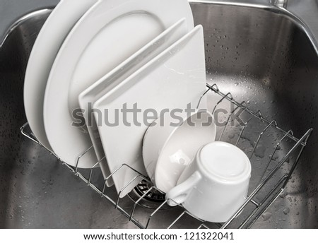White clean dishes drying on a rack in the kitchen sink. - stock photo