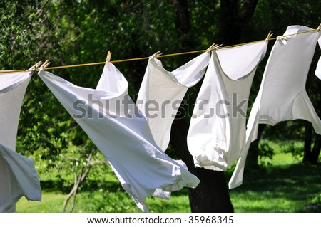white clean laundry hanging on the clothesline - stock photo