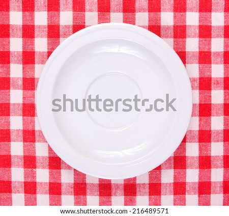 White clean plate on a red-white vichy tablecloth