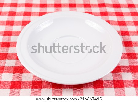 White clean plate on a red-white vichy tablecloth - stock photo
