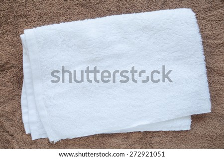 White clean towel on brown towel background - stock photo