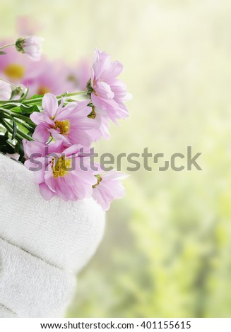White clean towels and fresh flowers with green natural background - stock photo