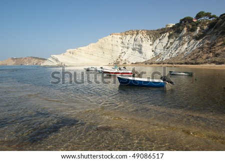 white cliffs and boats moored in the clear water of a sicilian bay - stock photo