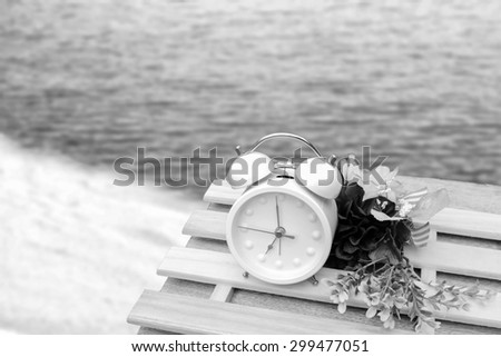 white clock and flower on the table with blur dark beach background ,black and white tone - stock photo