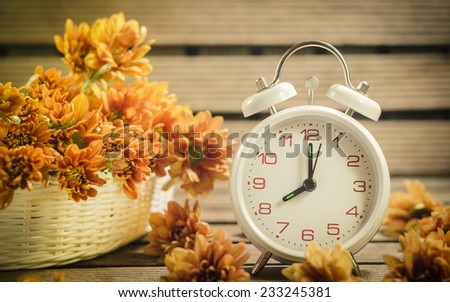White clock  chrysanthemum flower in the bowl and basket. On wooden background (Dendranthemum grandifflora) - stock photo