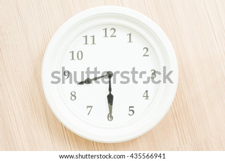 White clock on wood wall background.