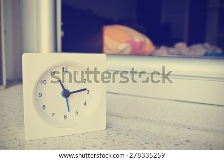 White clock with an empty bed in the background. Image filtered in faded, washed out, retro style; nostalgic, vintage travel concept.
