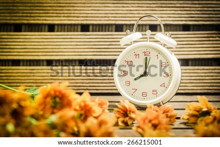 White clock with chrysanthemum flower in the  basket. On wooden background in vintage, retro tone .(Dendranthemum grandifflora) - stock photo