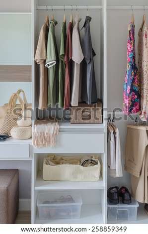 white closet with clothes, shirts, and accessories at home - stock photo