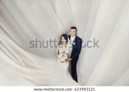 White cloth covers bride and groom posing in it