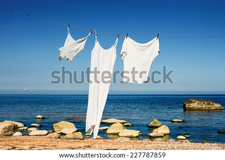 White clothes hanging on a rope on the sea beach - stock photo
