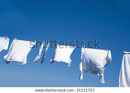 White clothes hanging on the line against blue sky. - stock photo
