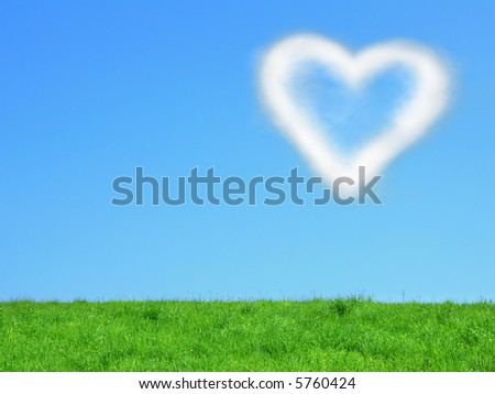 White cloud in the form of heart on blue sky with green grass at bottom of image. Symbol of love and happiness - stock photo