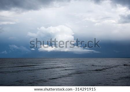 White cloud over dark Baltic sea. - stock photo