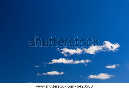 White clouds against a deep blue sky, may be used as background - stock photo