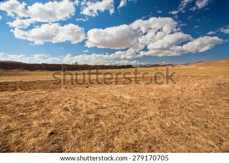 White clouds floating over dry grass land of plateau in Middle East  - stock photo