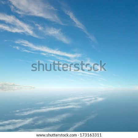 white clouds in the sky reflected in the water