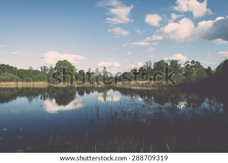 White clouds on the blue sky over blue lake with reflections - retro vintage film look