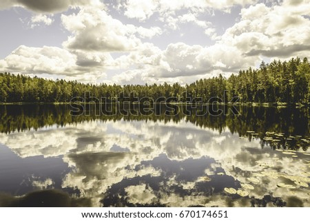 White clouds on the blue sky over forest lake with reflections - vintage old effect