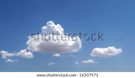 White clouds sitting in blue sky. - stock photo