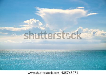 White clouds, sun beams on a blue sky over summer sea with sunlight reflection, Bali, Indonesia. Sunny sky with fantastic clouds and blue sea. Summer sunny sea. Summer Bali sea. Summer sea. Calm sea - stock photo
