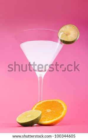 White cocktail with citrus over pink background - stock photo