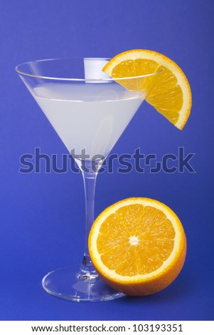 White cocktail with fresh oranges over blue background