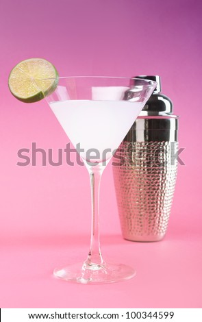 White cocktail with lime and shaker on pink background