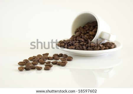 White coffee cup and coffee beans on a light background