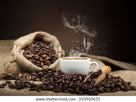 White coffee cup and coffee beans on burlap textile and brown background. - stock photo