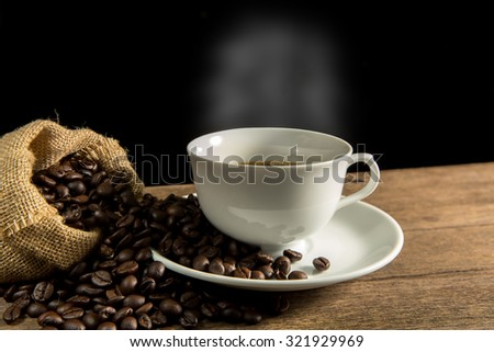 White coffee cup and coffee beans on wood background.