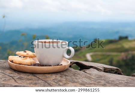 White coffee cup and cookies on wooden table with beautiful mountain view - stock photo