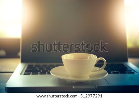 white Coffee cup and laptop for business in cafe