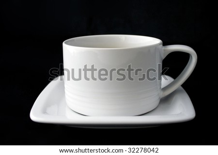 White coffee cup and plate isolated on black background