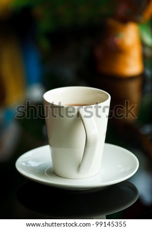 White coffee cup and reflection on table - stock photo