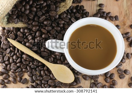 White coffee cup and roasted coffee beans on wood background.