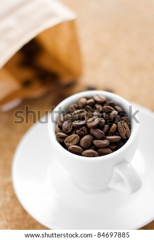 White coffee cup full of coffee beans