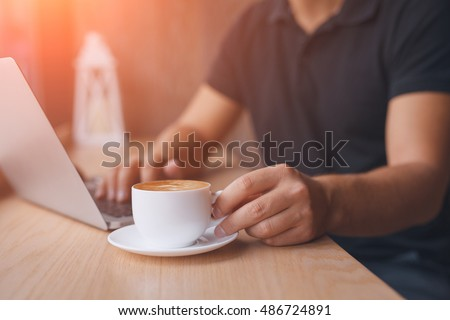 White coffee cup in focus. Unrecognizable man drinking hot coffee. Lens flare style effect picture