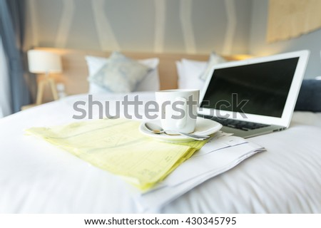 White coffee cup on bed - stock photo