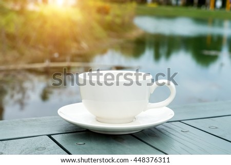 White coffee cup on green table in the morning with sunlight.