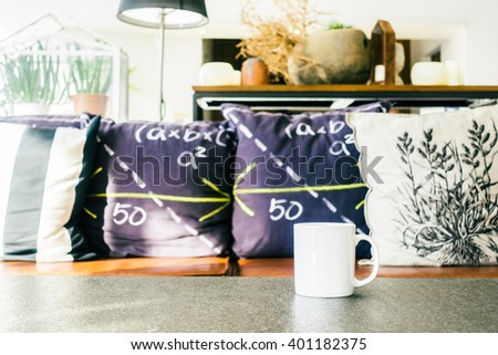 White coffee cup on table with sofa pillow decoration interior of living room - Vintage Light Filter