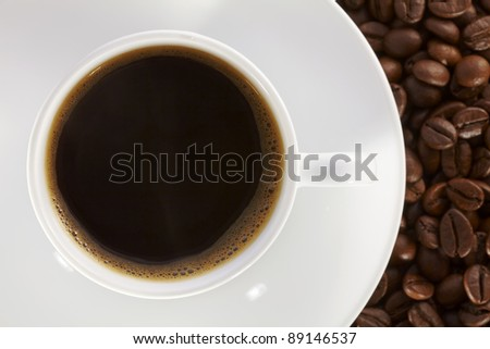 White coffee cup on the background of fresh baked coffee beans. - stock photo