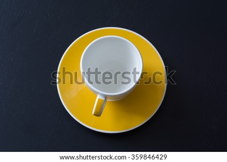 White coffee cup on the saucer yellow - stock photo