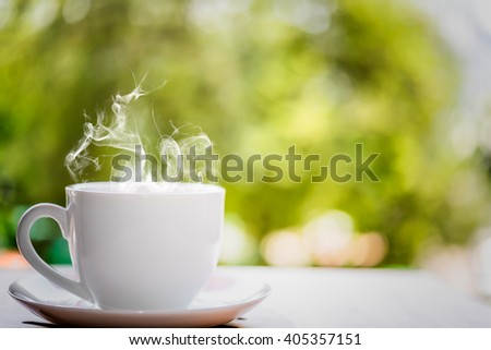 White coffee cup on top wooden table with blurred background - stock photo