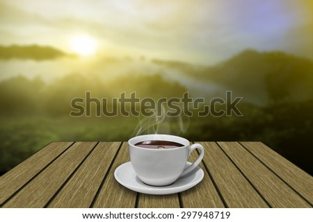 White coffee cup on vintage wooden with mountain and fog background in the early morning