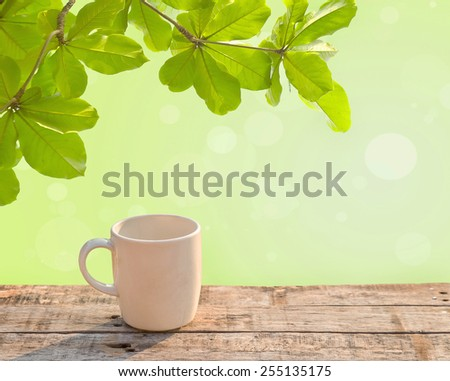White coffee cup on wooden table at morning sunlight and green leave background - stock photo