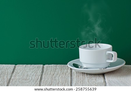 White coffee cup on wooden table with smoke - stock photo